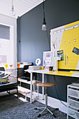 Desk and yellow-and-white pinboard against dark grey wall of teenager's bedroom