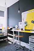 Schreibtisch mit gelb-weißer Pinnwand vor dunkelgrauer Wand in Jugendzimmer