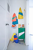 Small locker and brightly coloured cloth bags on hooks in white-tiled niche