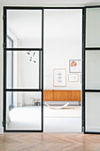 Glass-and-steel door leading to room with baby bouncer and retro sideboard