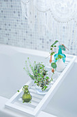 Vases of leaves on bathtub caddy