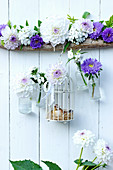 Small bottles and cage holding dahlias and asters suspended from branch
