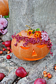 Carved pumpkin, wreath of pepper and shrub verbenas