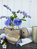 Spring arrangement of blue violas and peppermint flowers