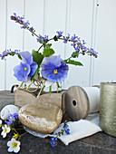 Spring arrangement of blue violas and peppermint flowers