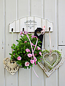Heart ornament and pink mini petunias on wooden wall