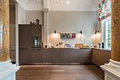 Modern, open-plan kitchen with pillars in Wilhelmine-era villa