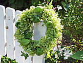 Wreath of hydrangea flowers and physalis lanterns on wooden fence