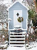 Stilt house in snowy winter garden