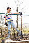 Boy standing proudly with spade in newly made raised bed in garden