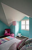 Bed and hot-pink chair in room with pale blue walls