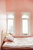 Metal bed below two small arched windows in pink bedroom