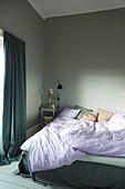 Rumpled bed in grey bedroom