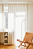 Folding chair with cane backrest and seat in front of window with translucent curtains