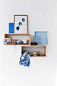 Bowls and handmade pictures in blue and white on wooden shelves