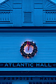 Christmas wreath with lights on outside wall of building at twilight