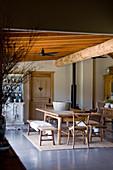 Wooden table, benches and chairs in rustic dining room with wooden ceiling beams
