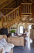 Rattensessel mit Tierfell und Kommode unter Treppe in offenem m Wohnraum