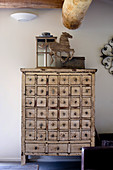 Lantern and horse sculpture on top of vintage apothecary cabinet