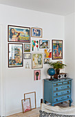 Collection of pictures on wall above blue vintage chest of drawers