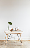 Office supplies on tray and Swiss cheese plant leaf in vase on pale wooden desk