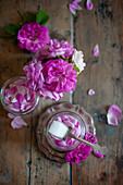 Pinkfarbene Rosenblüten mit Zucker im Schraubglas