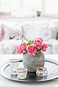 Vase of roses (variety: Leonardo da Vinci) and tealight holders on tray