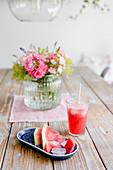 Watermelon, lemonade and vase of garden flowers on wooden table