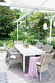 Summer terrace with seating area and climbing roses on a pergola