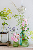 Roses, lady's mantle, fennel, lavender and strawberries in glass vases