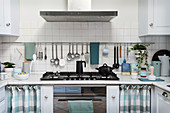 Utensils hung from rod on white-tiled wall above kitchen counter
