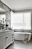 Washstand and free-standing bathtub in bathroom with louvre blind on window