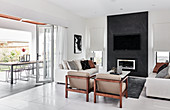 Sofas and armchairs in front of fireplace and TV on black wall in bright interior