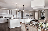 U-shaped kitchen counter with bar stools below pendant lamps and dining area in foreground of bright kitchen