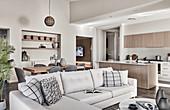 Helle Sofagarnitur mit Kissen, im Hintergrund Essbereich und Küche