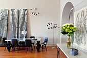 Flowers on console table, arched doorway and dining area in open-plan interior
