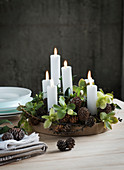 Arrangement of candles, pine cones and hellebore flowers