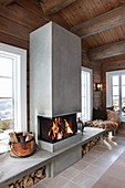 Fire in open fireplace flanked be masonry benches below windows