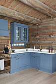 Blue cupboards in large country-house kitchen of log cabin