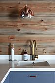 Copper-coloured spherical lamp above sink in country-house kitchen