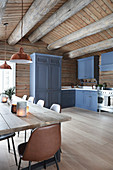 Blue cupboards and dining table in country-house kitchen of log cabin