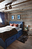 Blue bed with storage drawers and fur rug in log cabin