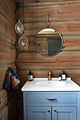 Blue sink unit in bathroom of log cabin