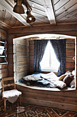 Cosy cubby bed with window in rustic log cabin
