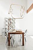 Verschiedene Designerstühle am Holztisch unterm Lichtobjekt