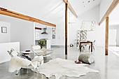 Sessel und Kuhfell im offenen Wohnraum mit Betonboden