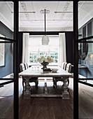 Blick durch offene Glas-Stahl-Tür ins elegante Esszimmer im Altbau