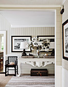 Bouquet of flowers and table lamps on white console table in hallway area