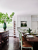 Cottage-style eat-in kitchen with dining table and green antique upholstered chairs