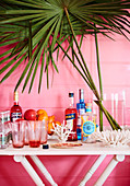 Home bar on white table in front of pink wall decorated with coral and palm fronds